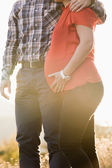 Close-up of pregnant woman and husband in sunset light — Stock Photo