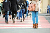 Close-up of woman legs waiting at a pedestrian crossing — Stock Photo