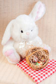 Cute easter bunny and easter eggs in basket — Zdjęcie stockowe
