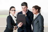 Business man and two coworkers looking worried over a flip chart — Stock Photo
