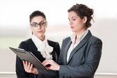 Two business women looking at flip chart — Stock Photo