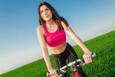 Beautiful woman biking on green field with blue sky background — Stock Photo