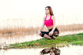 Young woman doing yoga in nature — Stock Photo