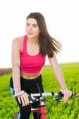 Young attractive woman on bike — Stock Photo