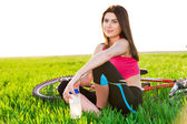 Attractive sports woman resting near bike holding a bottle of water — Stock Photo