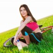 Young Woman Resting with Bike on the Beautiful field holding a bottle of water — Stock Photo