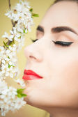 Close up of young woman and blossomed tree branch — ストック写真