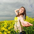 Portrait of woman reaching for camera in yellow rapeseed field — Stock Photo #45563409