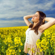 Portrait of woman relaxing in yellow colored field — Stock Photo