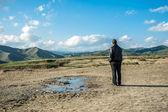 Człowiek stojący samotnie w błotnistej wulkany — Zdjęcie stockowe