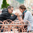 Young couple joking and doing skandenberg ovr coffee shop table — Stock Photo #46076095
