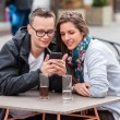 Couple looking on smartphone while sitting at coffee shop table — Stock Photo #46076135