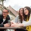 Three friend socializing at restaurant table — Stock Photo
