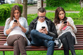 Focused group of friends looking on their phones and not socializing — Stock Photo