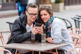 Couple looking on smartphone while sitting at coffee shop table — Stock Photo