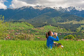 Young woman resting on hill with beautiful mountain scenery on background — ストック写真