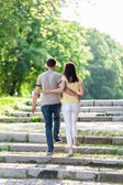 Young woman and man walking in city park holding hands — Stock Photo