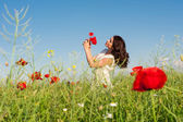 Beauty woman in poppy field in white dress holding a poppies bouquet — Foto Stock