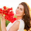 Beautiful Girl over Sky and Sunset in the field holding a poppies bouquet, smiling — Stock Photo #47310679
