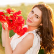 Beautiful lady over Sky and Sunset in the field holding a poppies bouquet, smiling — Stock Photo #47310687
