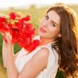 Beautiful lady over Sky and Sunset in the field holding a poppies bouquet, smiling — Stock Photo