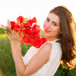 Free Happy Woman Enjoying Nature in the field holding a poppies bouquet — Stock Photo #47310691