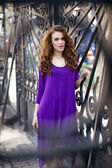 Beautiful young woman with violet dress — Stock Photo
