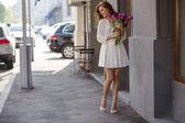可爱的小女孩的白裙子和一束美丽的郁金香. — 图库照片