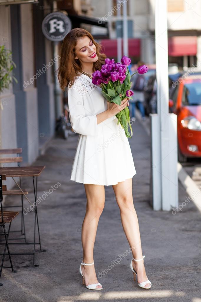 可爱的小女孩的白裙子和一束美丽的郁金香