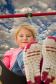 Young girl at the park swinging — Stock Photo
