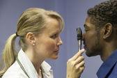 Caucasian female doctor examines and gives physical to african american male — Stock Photo