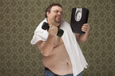 Overweight male holding scales working hard to lose weight — Stock Photo