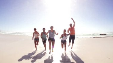Friends running and jumping to camera on beach — Vídeo Stock