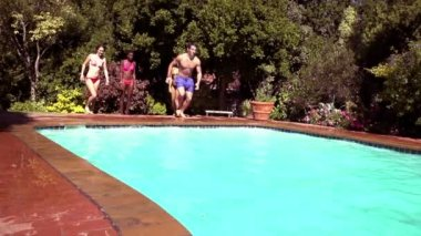 Friends jumping into a pool — Stock Video