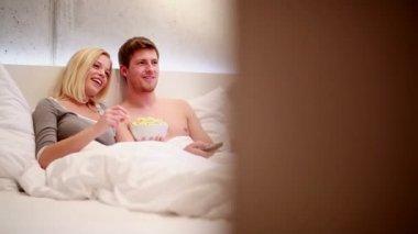 Casal na cama assistindo tv e comendo pipoca — Vídeo stock