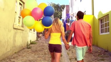 Couple walking together in alley with colorful balloons — Stock Video