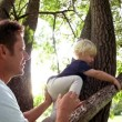 Father helping son to climb tree — Stock Video