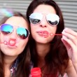 Girls with sunglasses having fun making bubbles — Stock Video #45156085