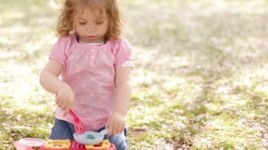 Little girl with play kitchen in the park — Stock Video