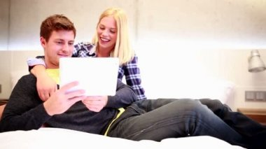 Couple sitting on bed with tablet computer — Stock Video