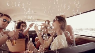 Hipsters blowing bubbles in camper van — Stock Video