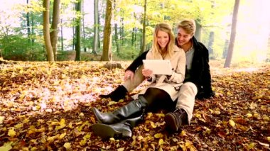 Couple with tablet computer in autumn park — Stock Video