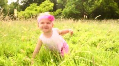 Baby flicka kryper genom gräs — Stockvideo