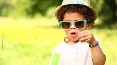 Boy having fun blowing soap bubbles — Stock Video