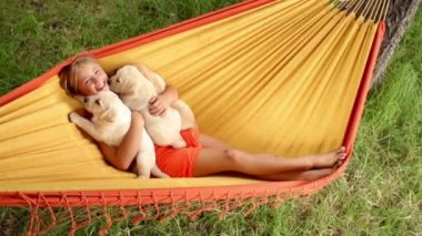 Happy girl holding labrador puppies while swinging in hammock — Stock Video