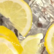Ice cubes and lemon slices falling into jug of water — Stock Video