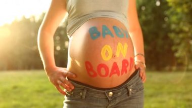 "Pregnant woman with ""baby on board"" written on baby belly — Stock Video"