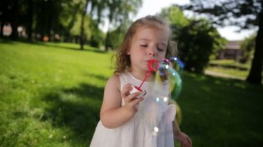 Little girl having fun blowing soap bubbles — Stock Video
