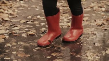 Child in rubber boots jumping in the puddle — Stockvideo