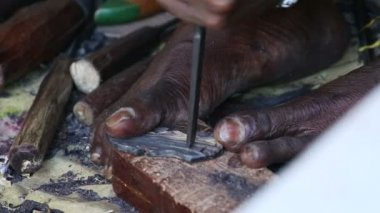 African carver creating a souvenir for tourists — Stock Video
